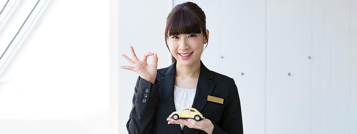 ミニチュアカーを手に持って笑顔を見せる若い女性